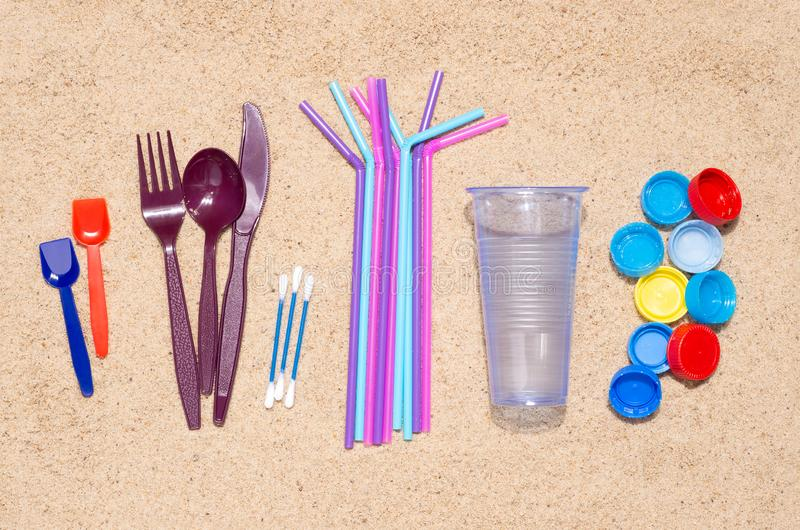 Disposable single use plastic objects that cause pollution of the environment, especially oceans. Top view on sand stock photography
