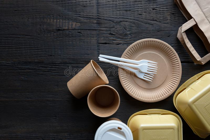 Disposable takeaway food boxes and tableware on dark wooden background. Nature friendly kitchen utensil. In a natural light royalty free stock image