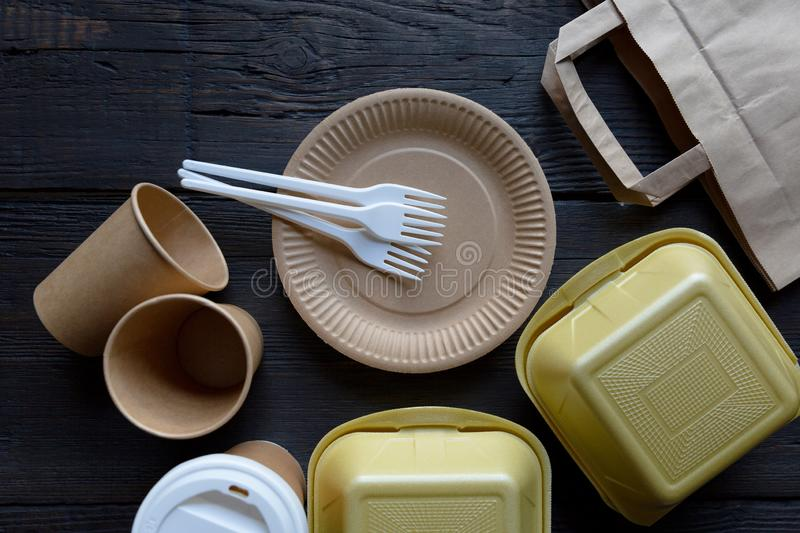 Disposable takeaway food boxes and tableware on dark wooden background. Nature friendly kitchen utensil. In a natural light stock image