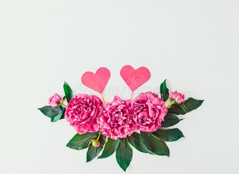 Disposi??o com composi??o das flores da pe?nia e dois cora??es no fundo branco Amor, casamento Modelo floral da textura do Valent imagens de stock