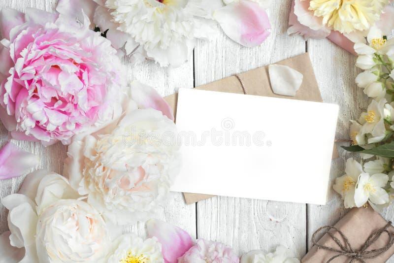 A disposição criativa feita da peônia, cor-de-rosa e do jasmim floresce com cartão e a caixa de presente vazios imagem de stock royalty free
