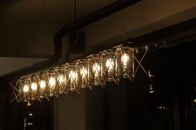 Disposição de candelabros leves claros sob a atmosfera escura fotografia de stock royalty free