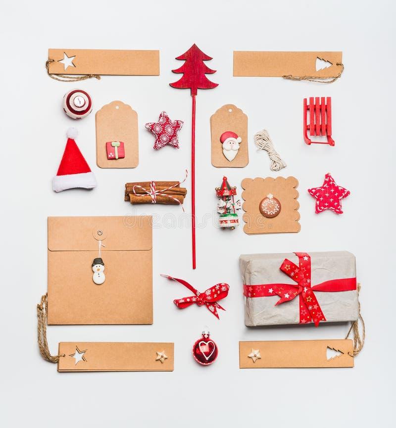 Disposição do Natal com as caixas de presente de envolvimento de papel do ofício, etiquetas, cookies, decoração vermelha do feria imagem de stock royalty free
