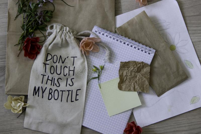 Disposição manual com flores, papel e um saco pequeno imagens de stock