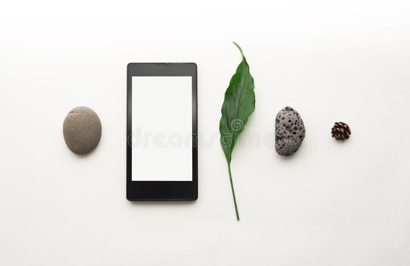 Disposici?n creativa del tel?fono m?vil de la maqueta Smartphone puesto plano, papel de nota en blanco Fondo blanco de la tabla M foto de archivo libre de regalías