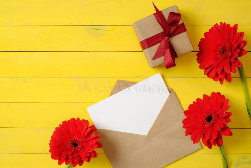 Disposición creativa hecha de sobre del papel del vintage con la tarjeta en blanco, las flores rojas de la margarita y la pequeña imagen de archivo libre de regalías