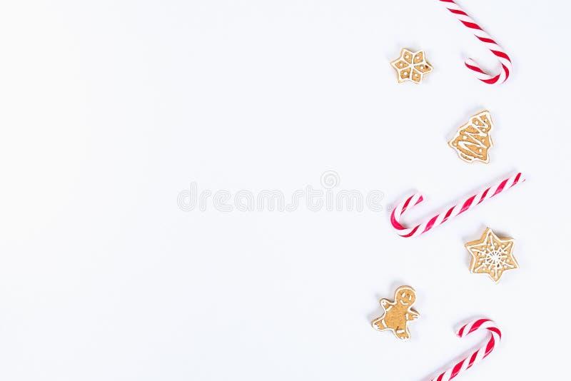 Disposición de la Navidad Caramelos rojo-blancos rayados del bastón y galletas hechas en casa del jengibre en un fondo blanco Año imágenes de archivo libres de regalías