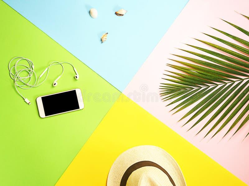 Disposición de los accesorios del viajero de la visión superior: hoja de palma tropical, sombrero de paja blanco, teléfono móvil  imagen de archivo libre de regalías