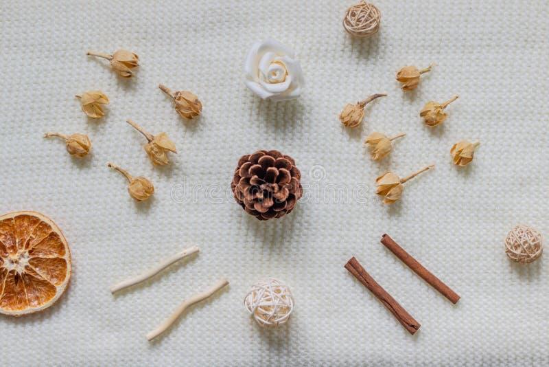 Disposición de una bufanda blanca o de una manta texturizada, de lana Especias, flores secadas, fruta cítrica, cono del pino Otoñ imagenes de archivo
