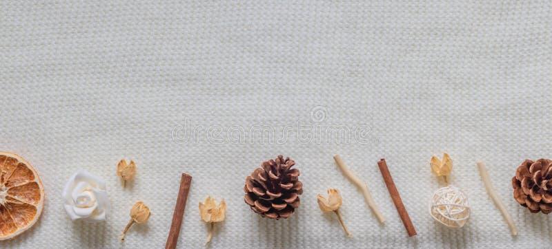 Disposición de una bufanda blanca o de una manta texturizada, de lana Especias, flores secadas, fruta cítrica, cono del pino Otoñ fotografía de archivo