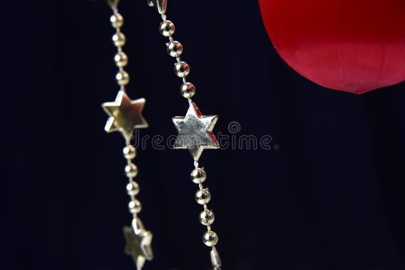 Disposición navideña con bolas rojas y adornos rojos colgados aislados en fondo negro ilustración del vector