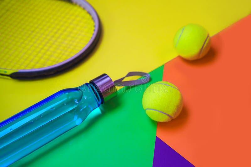 Disposici?n con las pelotas de tenis, estafa, botella del tenis de agua en diverso fondo de ne?n multicolor del extracto con el l imagenes de archivo