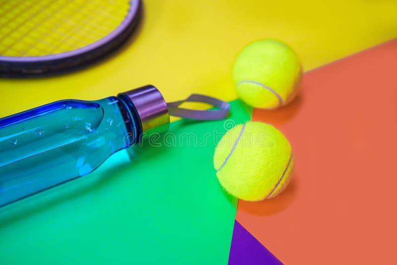Disposici?n con las pelotas de tenis, estafa, botella del tenis de agua en diverso fondo de ne?n multicolor del extracto con el l foto de archivo