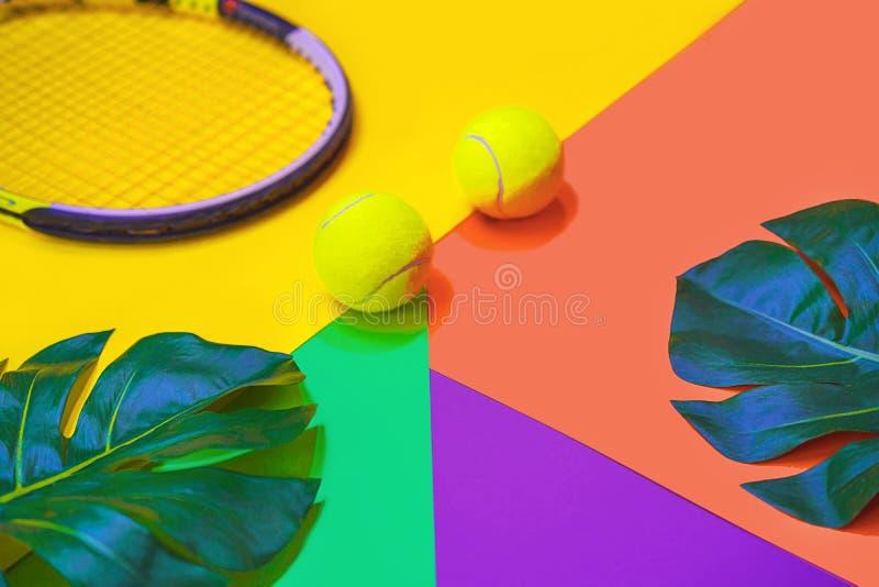 Disposici?n del tenis con las pelotas de tenis, la estafa y las hojas tropicales del monstera en diverso fondo de ne?n multicolor fotos de archivo