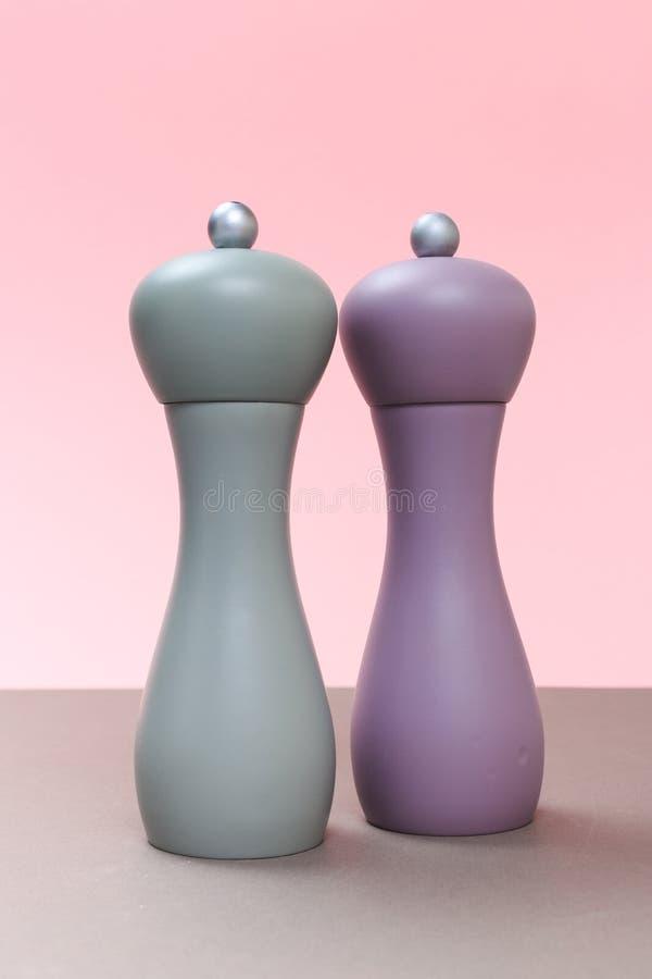 Dispositif trembleur de sel et de poivre sur le conseil gris et un fond rose photographie stock