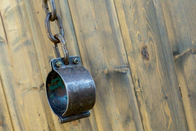 Dispositifs d'accrochage noirs en métal avec le vieil équipement de chaîne décourageant des criminels et des menottes forgées méd images stock