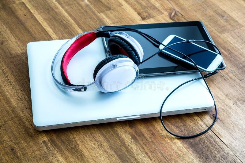 Dispositifs et écouteurs de Digital sur un bureau en bois images libres de droits