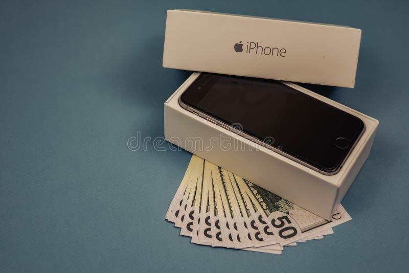 Dispositifs et dollars d'iPhone d'Apple sur un fond monophonique bleu Voronezh, Russie - 3 mai 2019 images stock