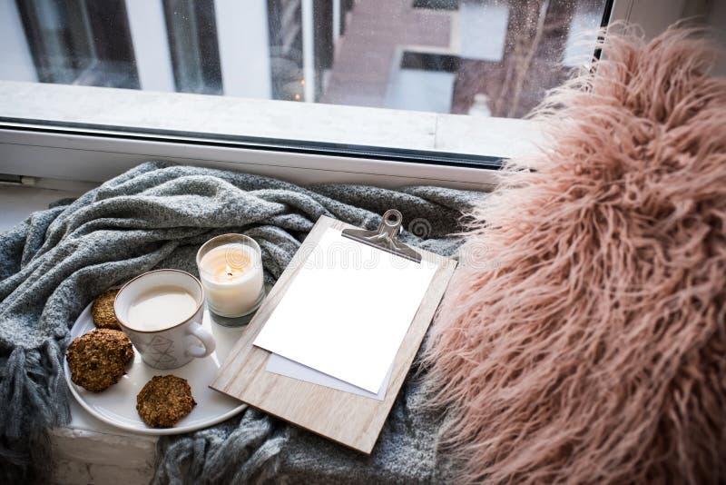 Disposition à la maison confortable avec la tasse de café et la maquette vide de presse-papiers photographie stock