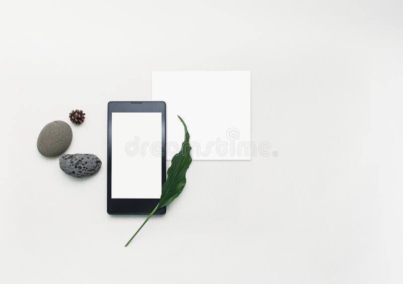Disposition cr?ative de t?l?phone portable de maquette Smartphone ?tendu plat, papier de note vide Fond blanc de table Moquerie d images libres de droits