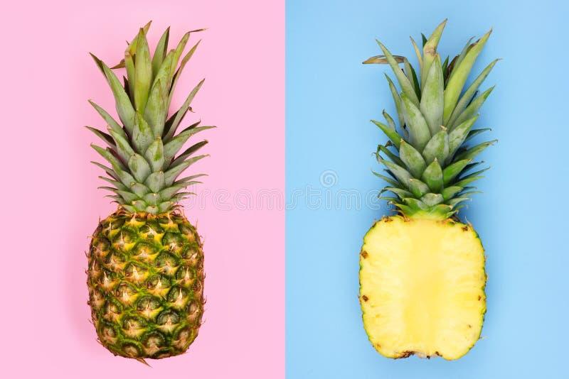 Disposition d'ananas avec le fruit entier sur le rose en pastel et la demi tranche sur le bleu images stock
