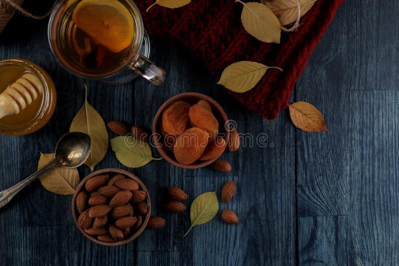 Disposition d'automne avec des amandes, des abricots secs, thé, miel et une écharpe chaude et feuilles de jaune sur une table en  photo stock