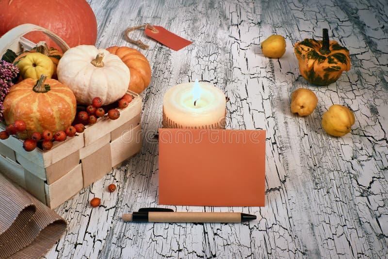 Disposition d'automne avec les potirons, la bougie brûlante et l'envel vide images libres de droits