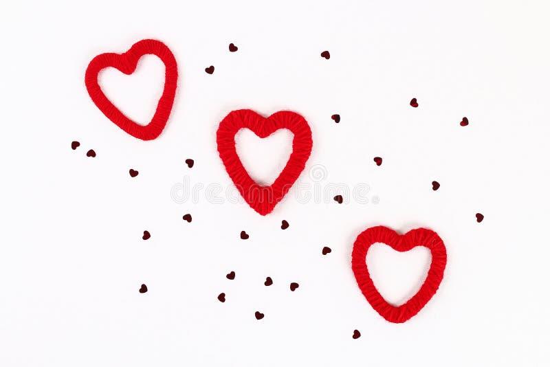 Disposition de Saint Valentin Coeurs diy faits maison rouges faits de carton et fil sur un fond blanc Jour de valentines de St d' photos stock