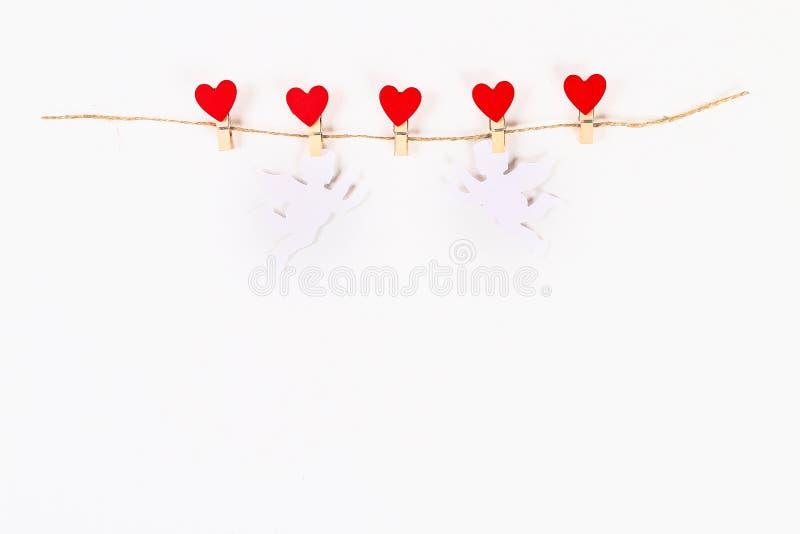 Disposition de Saint Valentin Coeurs rouges et cupidons blancs sur la ficelle en bois de jute de pinces à linge sur le fond blanc image stock