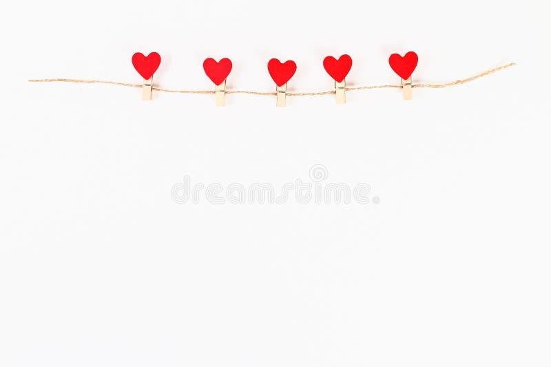 Disposition de Saint Valentin Coeurs rouges sur les pinces à linge en bois sur une ficelle de jute sur un fond blanc Jour de vale photo stock