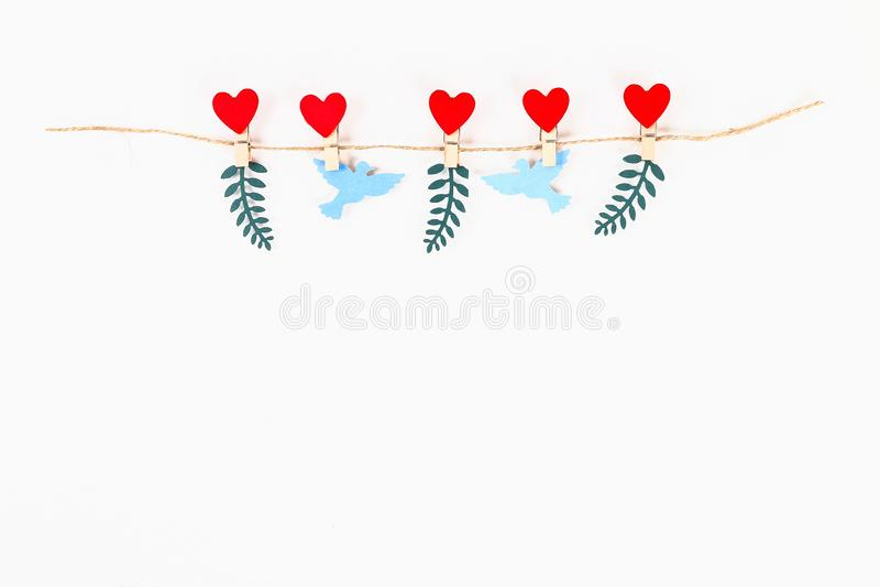 Disposition de Saint Valentin Le coeur et les colombes rouges aiment sur les pinces à linge en bois sur la ficelle de jute sur le photo libre de droits
