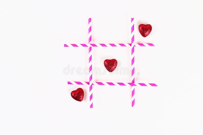 Disposition de Saint Valentin Riens et pailles et coeurs roses de croix sur un fond blanc Tep de Tic Tac Jour de valentines de St image stock