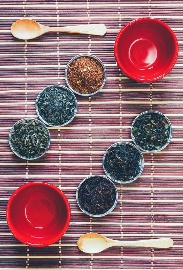 Disposition des feuilles de thé de différentes variétés de tasses rouges et de cuillères en bois sur le tapis en bambou photos libres de droits