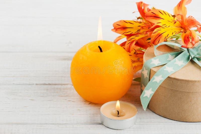 Disposition des fleurs de lis et de la bougie oranges, boîte-cadeau image libre de droits