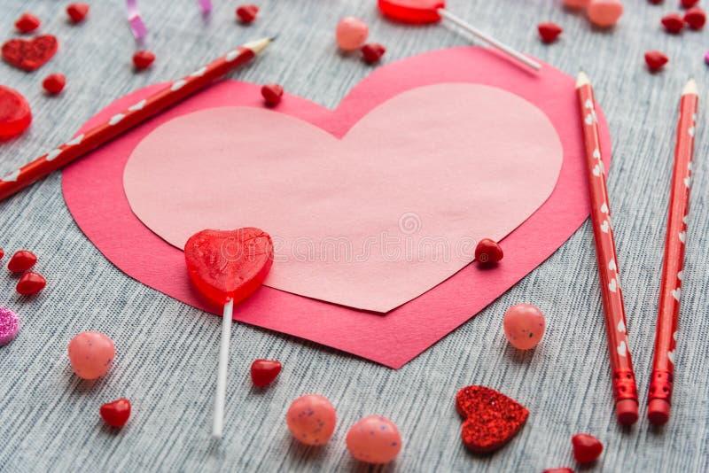 Disposition plate de configuration du coeur de papier rose et rouge se trouvant sur la table avec les crayons rouges et les sucre photo libre de droits