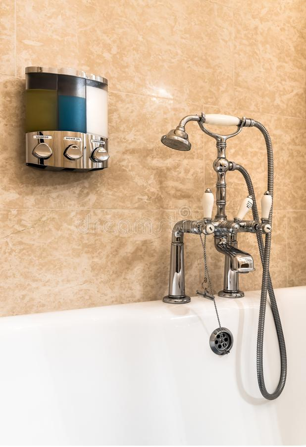 Dispositivi d'annata della vasca con la testa di doccia flessibile ed il contenitore con i saponi da bagno liquidi sulla parete fotografia stock libera da diritti