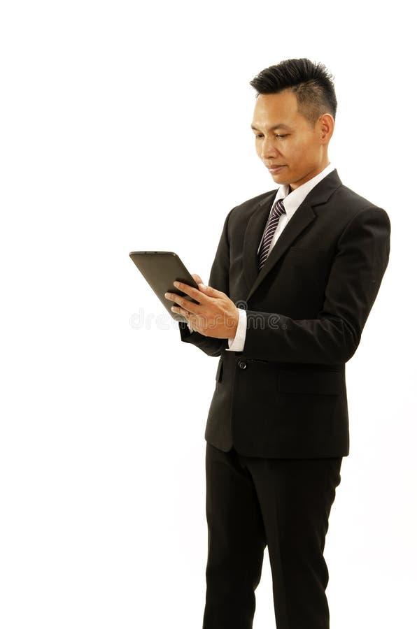 Dispositivo asiático de la tableta de la tenencia de la mano del hombre de negocios en el backgroun blanco imágenes de archivo libres de regalías