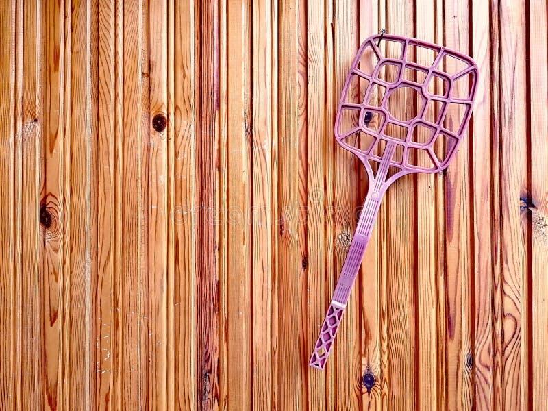 Dispositivo de bolsillo para sacudir hacia fuera el polvo de las alfombras y solarlo contra un fondo de tableros de madera marron imagenes de archivo