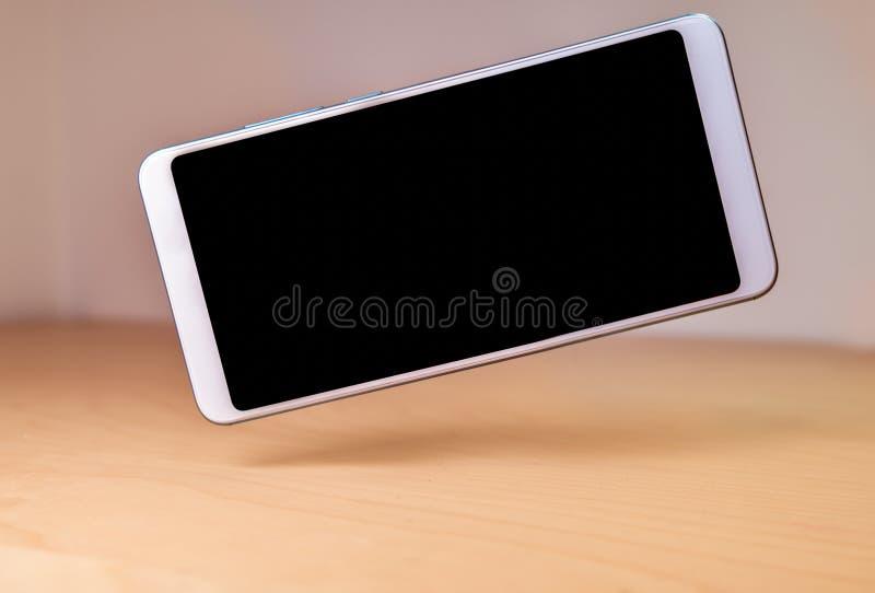 Dispositivo de Smartphone que flota o que eleva y mantiene flotando sobre una tabla de madera fotos de archivo