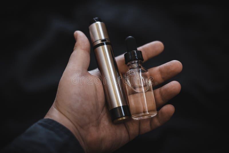 Dispositivo de Vaping adentro en la mano del ` s del hombre Cigarrillo electrónico, vape imagenes de archivo