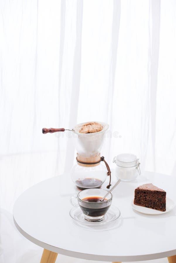 Dispositivo di gocciolamento del caffè americano e gocciolare caffè macinato con il vaso del gocciolamento, la tazza ed il dolce  immagini stock libere da diritti
