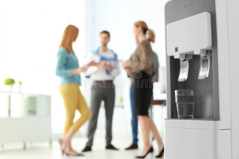 Dispositivo di raffreddamento di acqua moderno con gli impiegati di ufficio di vetro e vaghi su fondo immagine stock libera da diritti