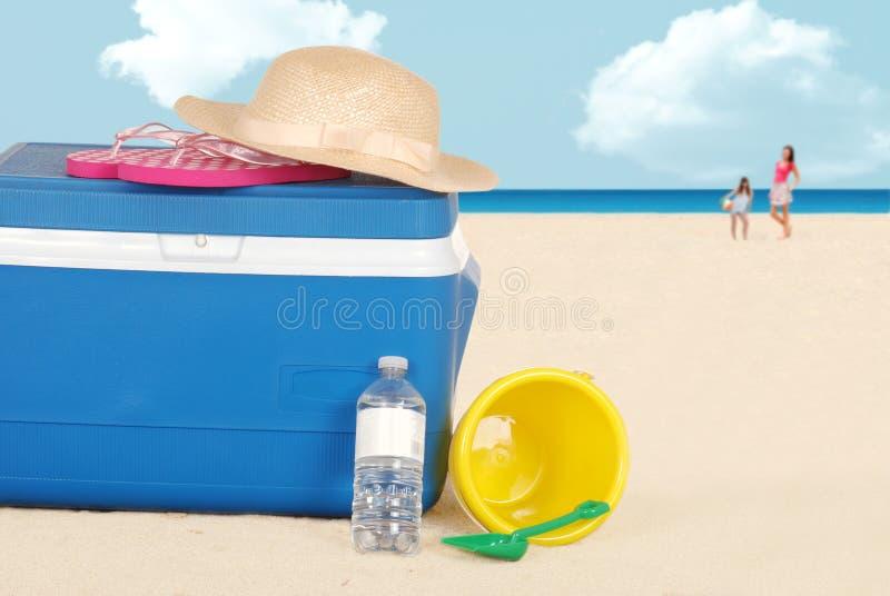 Dispositivo di raffreddamento della spiaggia con acqua di bottiglia e del cappello fotografia stock