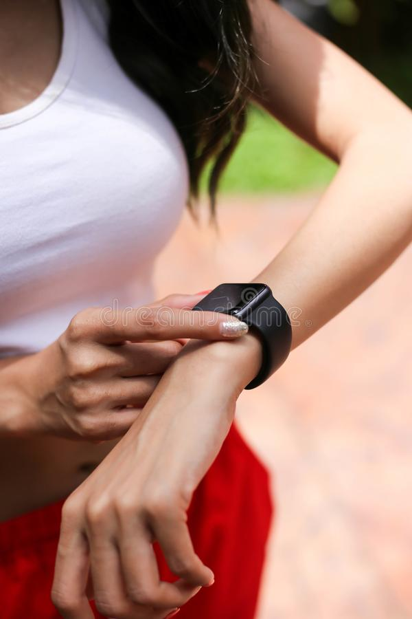 Dispositivo esperto do relógio do desgaste do olhar da jovem mulher do esporte da saúde que verifica p fotografia de stock royalty free