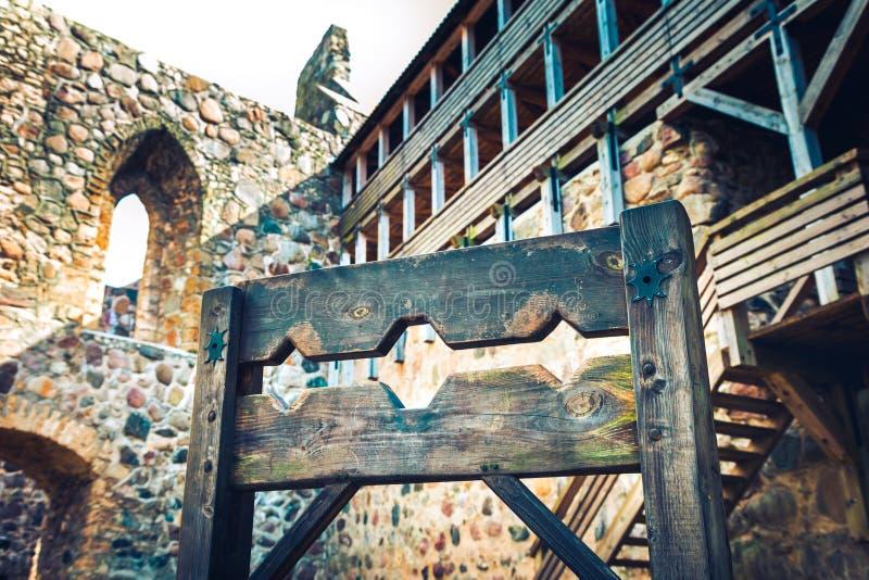 Dispositivo medieval de madera de la tortura, picota antigua en castillo foto de archivo