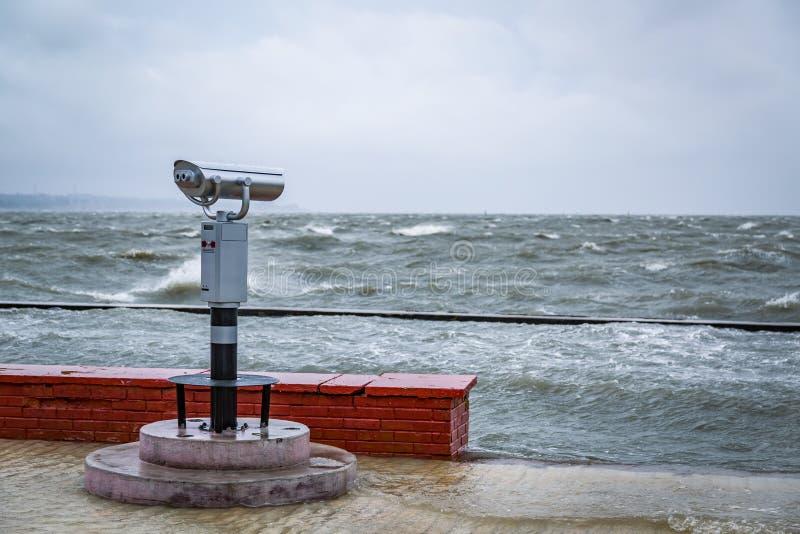 Dispositivo ottico fisso per fare un giro turistico installato sull'argine durante la tempesta immagini stock