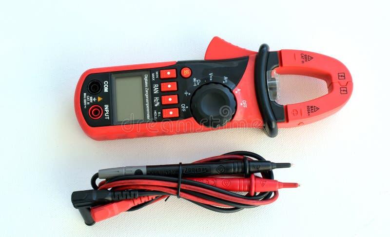 Dispositivo per la misurazione della tensione in uno sbocco elettrico con un multimetro su un fondo bianco attrezzatura, apparato fotografia stock