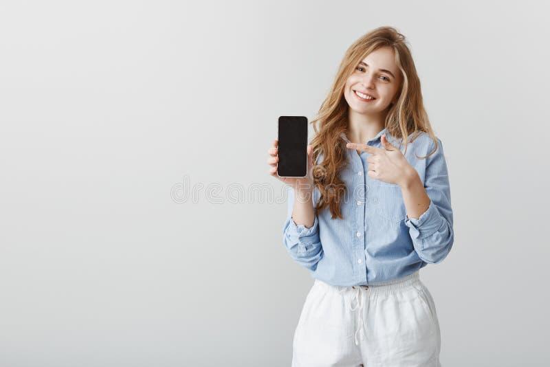 Dispositivo utile eccellente Lo studio ha sparato di bella studentessa piacevole con capelli biondi in camicia manuale, mostrando immagine stock