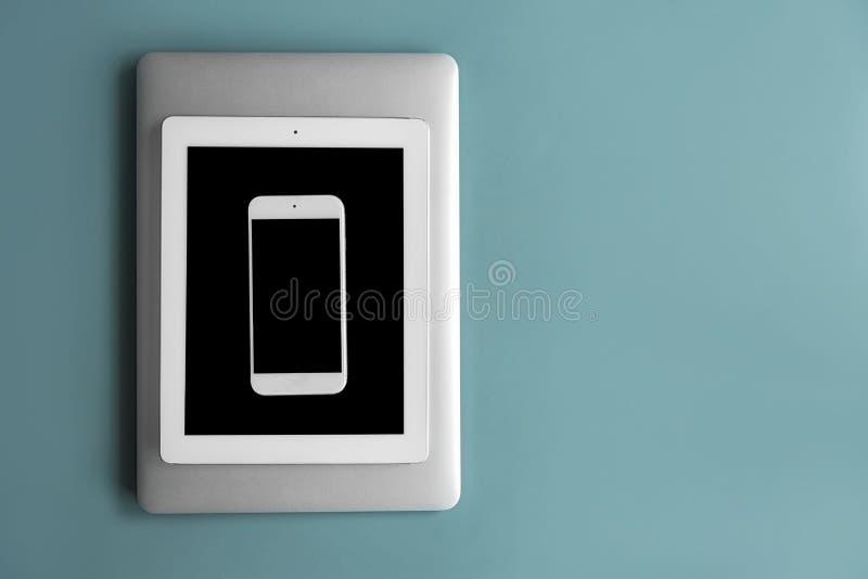 Dispositivos com as telas vazias no fundo da cor, fotografia de stock