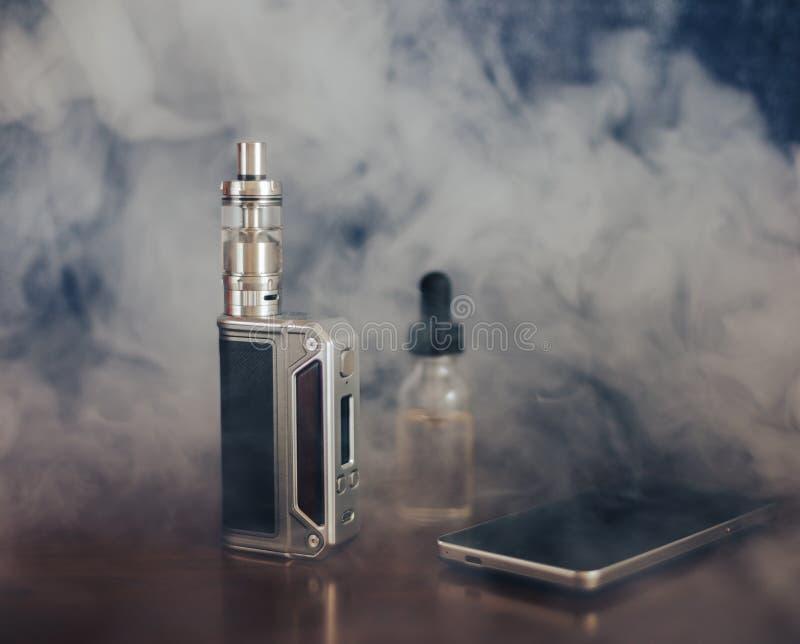 Dispositivos de Vape, E-cigarrillo para vaping, líquido en la botella y teléfono móvil imagen de archivo libre de regalías